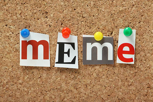 The word Meme in magazine letters pinned to a cork notice board. Meme is used to describe a piece of information or an element of culture in various media.