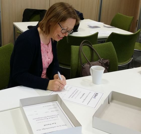Co Chair Dr Carina Buckley signs professional accreditation certificates