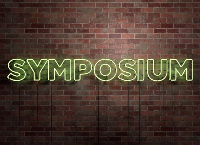 Brick wall with the word symposium in neon lights