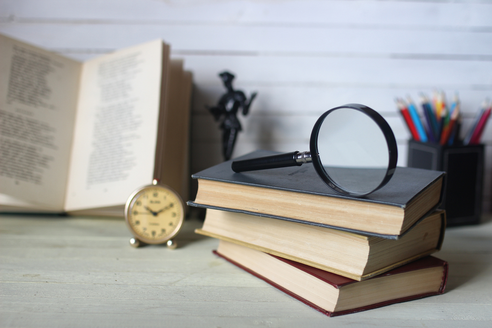 Pile of books with a magnifying glass on top