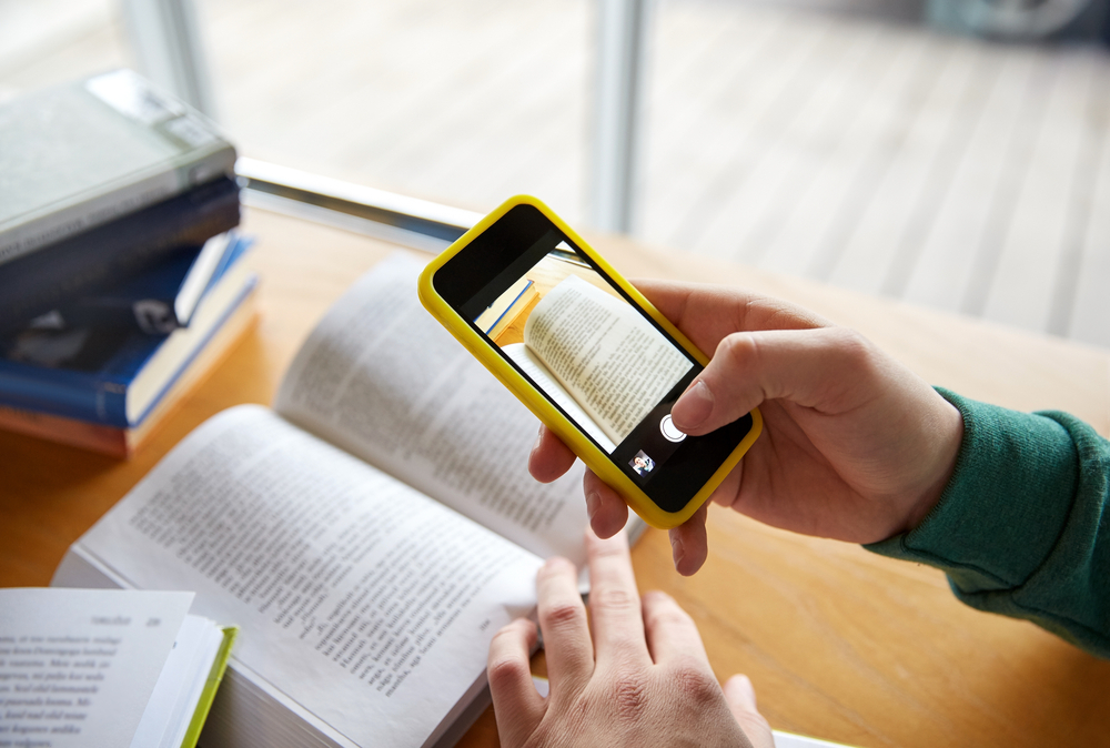 close up of student hands with smartphone taking picture of books page and making cheat sheet in school library